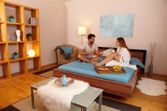Homem feliz e mulher que comem o pequeno almoço na cama Fotografia de Stock Royalty Free