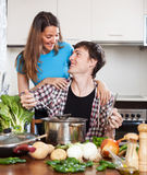 Homem feliz e mulher que cozinham a sopa Fotos de Stock Royalty Free