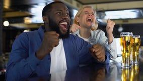 Homem feliz e mulher que olham o fósforo em linha dar a elevação cinco, objetivo satisfeito da equipe video estoque