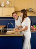 Homem feliz e mulher que sorriem na cozinha Fotografia de Stock