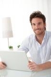 Homem feliz em casa com computador Imagem de Stock