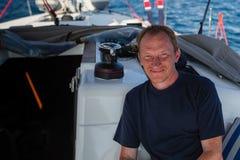 Homem feliz em seu barco do iate da navigação no mar Curso imagem de stock