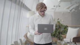 Homem feliz louro bem sucedido do retrato nos vidros que dançam em um dispositivo confortável leve da terra arrendada do escritór video estoque
