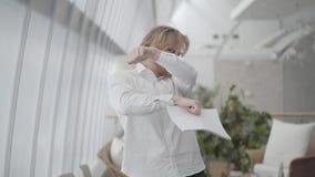 Homem feliz louro nos vidros que dançam em um escritório confortável claro que guarda papéis nas mãos O chefe joga documentos aci vídeos de arquivo