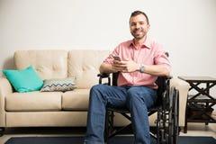 Homem feliz na cadeira de rodas com um telefone Fotografia de Stock Royalty Free