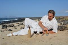 Homem feliz na praia com dois vidros do vinho tinto Imagem de Stock