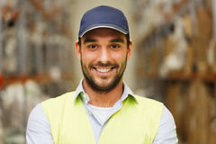 Homem feliz na veste reflexiva da segurança no armazém Fotos de Stock Royalty Free