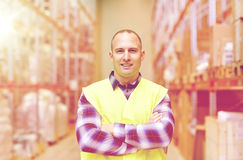 Homem feliz na veste reflexiva da segurança no armazém Fotografia de Stock Royalty Free