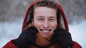 Homem feliz no revestimento do inverno com capa fora filme