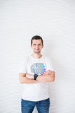 Homem feliz no t-shirt e na calças de ganga brancos em um fundo branco que olha a câmera fotografia de stock royalty free