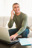 Homem feliz no telefone usando o portátil Fotografia de Stock Royalty Free