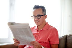 Homem feliz nos vidros que lê o jornal em casa imagens de stock