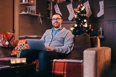 Homem feliz nos vidros vestidos no portátil morno da posse da camiseta e em olhar a câmera ao sentar-se no sofá no tempo do Natal fotos de stock royalty free