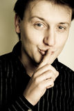 Homem feliz novo com seu dedo sobre sua boca Foto de Stock Royalty Free