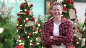 Homem feliz novo do moderno que sorri contra árvores de Natal fora video estoque