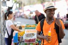 Homem feliz novo do turista do africano negro que guarda o suco de laranja foto de stock