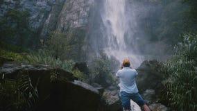 Homem feliz novo do turista da vista traseira que toma a foto do smartphone na grande cachoeira tropical cênico da selva de Sri L video estoque