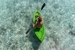 Homem feliz novo que kayaking em uma ilha tropical em Maldivas ?gua azul desobstru?da imagens de stock royalty free