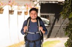 Homem feliz novo que veste a roupa ocasional e a trouxa que levantam para a câmera, sorrindo, ambiente do jardim, conceito do moc Fotografia de Stock