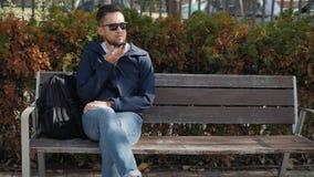 Homem feliz ocasional que usa o smartphone que senta-se em um banco no áudio do ajudante do discurso do ai do reconhecimento de v video estoque
