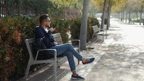 Homem feliz ocasional que usa o smartphone que senta-se em um banco no áudio do ajudante do discurso do ai do reconhecimento de v filme