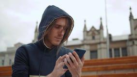 Homem feliz ocasional que usa um smartphone que senta-se em um banco em um estudante do parque na navegação das aplicações do tel filme