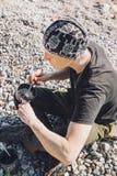 Homem feliz que acampa na praia e em comer Imagens de Stock Royalty Free