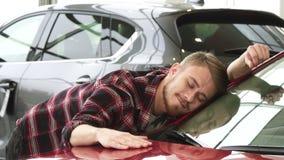 Homem feliz que afaga seu carro novo que sorri delicadamente mostrando os polegares acima no negócio filme