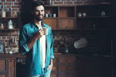 Homem feliz que aprecia seu café durante uma ruptura na cozinha Imagens de Stock Royalty Free