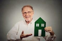Homem feliz que apresenta a casa verde Imagem de Stock Royalty Free