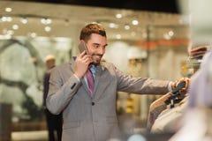 Homem feliz que chama o smartphone na loja de roupa Fotografia de Stock