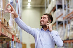 Homem feliz que chama o smartphone no armazém fotos de stock