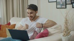 Homem feliz que comemora o sucesso com o laptop no sofá em casa video estoque