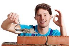 Homem feliz que constrói uma parede Fotografia de Stock Royalty Free