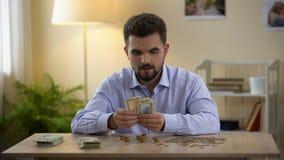 Homem feliz que conta moedas e notas de dólar em casa e que sorri, economias do orçamento filme