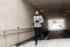 Homem feliz que corre ao longo do túnel do metro no inverno Foto de Stock Royalty Free
