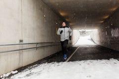 Homem feliz que corre ao longo do túnel do metro no inverno Fotos de Stock