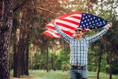 Homem feliz que corre com bandeira dos EUA Comemorando o Dia da Independência de América 4 de julho Homem que tem o divertimento Imagens de Stock