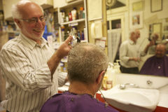Homem feliz que corta o cabelo do cliente superior com lâmina Fotos de Stock