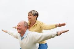 Homem feliz que dá às cavalitas à mulher Imagem de Stock