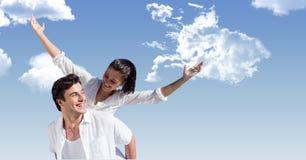 Homem feliz que dá às cavalitas o passeio à mulher contra o céu fotografia de stock