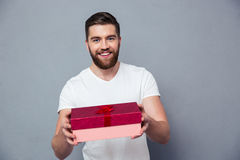 Homem feliz que dá a caixa de presente na câmera Fotografia de Stock