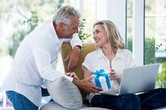 Homem feliz que dá o presente à mulher com portátil Fotografia de Stock Royalty Free