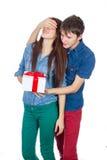 Homem feliz que dá um presente a sua amiga Pares bonitos novos felizes isolados em um fundo branco Imagens de Stock
