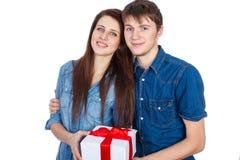 Homem feliz que dá um presente a sua amiga Pares bonitos novos felizes isolados em um fundo branco Fotografia de Stock Royalty Free
