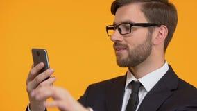 Homem feliz que enrola o smartphone, o cliente satisfeito com a rede e a qualidade da tarifa filme