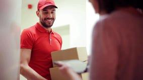 Homem feliz que entrega caixas do pacote à casa do cliente video estoque