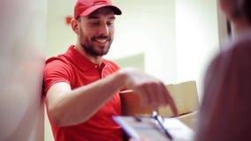 Homem feliz que entrega caixas do pacote à casa do cliente filme