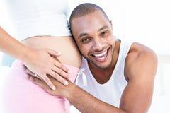 Homem feliz que escuta a barriga da esposa grávida fotos de stock