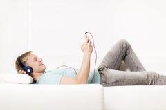 Homem feliz que escuta a música com fones de ouvido e descanso. fotos de stock royalty free